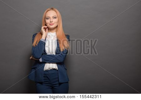 Portrait of happy smiling model woman with red hair posing isolated on grey background in studio. Fashion or vogue concept.