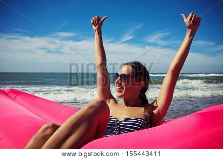 A female sitting on a deep-pink airbed on the beach holding her thumbs up and smiling. She is wearing a striped swimming suit and dark sunglasses, her hair is put in a braid.