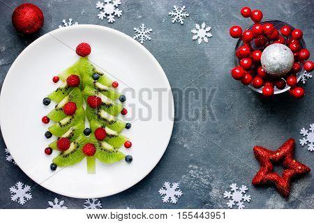 Healthy Christmas dessert snack breakfast for kids - kiwi blueberry raspberry Christmas tree top view
