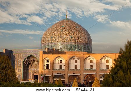 Sheikh Lotfollah Mosque in Naghshe Jahan or Imam Square of Isfahan which is one of the UNESCO World Heritage sites and is illuminated by a warm sunset.