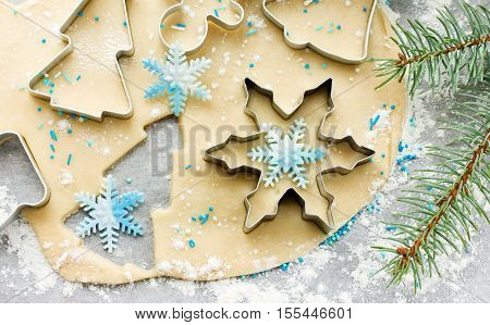 Christmas cookie preparation - raw dough christmas tree branch and cookie cutters