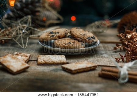 Beautiful concept. Chocolate cookies on a white plate on a wooden background. Nearby stands a Christmas tree, toys, tea, garlands and Christmas toys.