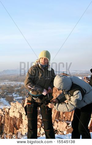 girl rock-climber on rock in winter