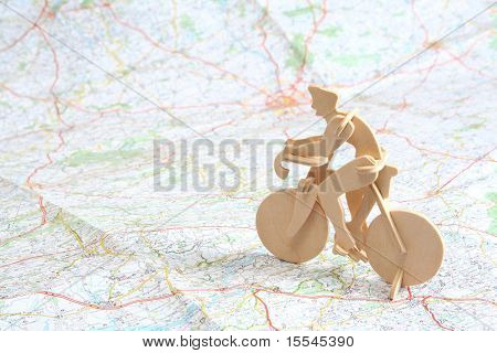 Wooden model of bicyclist on background of map