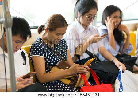 BANGKOK, THAILAND, SEPTEMBER 23, 2016 : Passengers using smartphone inside the public transportation in Bangkok, Thailand