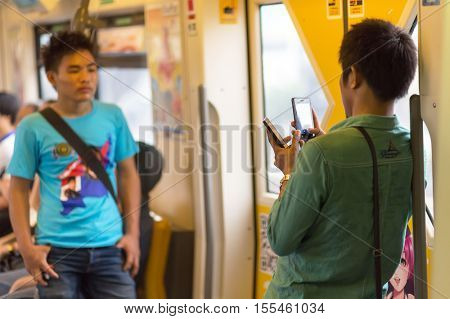 BANGKOK, THAILAND, SEPTEMBER 23, 2016 : Passengers using smartphone inside the public transportation in Bangkok, Thailand