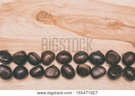 Chestnuts background. Brown Chestnuts on wooden  background