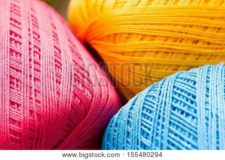 Colorful knitting thread texture, handiwork backdrop. Bright handiwork background, crochet iris pink, yellow and blue string, Leisure, hobby, needlework concept