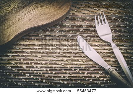 Fork and Knife on wooden table Vintage style.