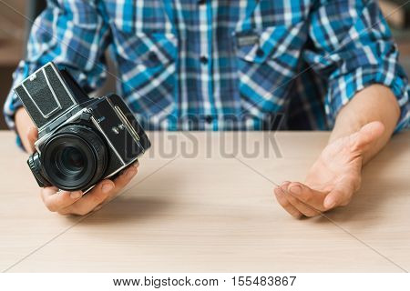 Photographer compare old camera with something, void. Free space in one empty hand of man, copy space for text. New technology advertisement background
