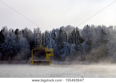 Ferry in wintertime. Mist rising from the sea. White icy trees on background. Place: Parainen, Finland.