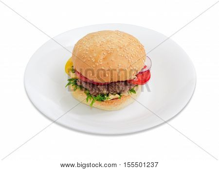 Traditional hamburger with beef patty vegetables and condiments on a white dish on a light background