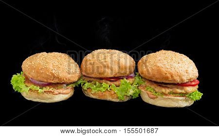 Three hamburgers with beef patty vegetables and condiments on a dark background