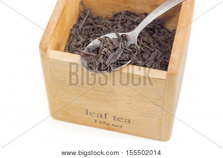 Loose dried large tea leaves of black tea in a tea spoon on the background of a wooden box with tea leaves on a light background closeup