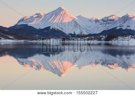 Reflects of the snowy mountains at the sunset in the Campotosto lake, Abruzzo - Italy.