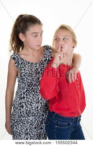 Two Teenage Girl Making Hand Gesture To Keep Things Quiet