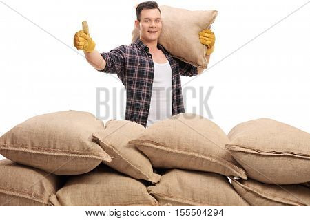 Young agricultural worker behind a pile of sacks holding a burlap sack on his shoulder and giving a thumb up isolated on white background