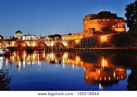 Rome Italy - Mausoleum of Hadrian and river Tiber at night on background St. Peter's Basilica dome in Vatican
