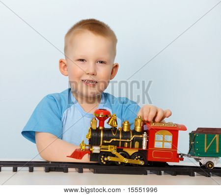 Little Boy Playing With A Toy Locomotive