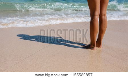 Low section shot of woman standing on the beach. Feet of a woman with shadow on the sea shore on a summer day.