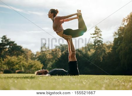 Fit Young Couple Doing Acro Yoga