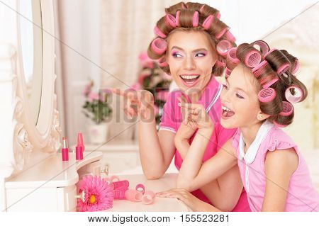 portrait of happy  Mother and little daughter in hair curlers near mirror