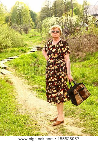 pensioner european woman with shopping bag close up photo full body length on summer path background