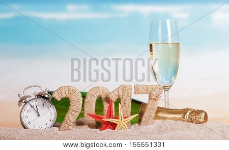 Figures 2017, a bottle of champagne and glass, alarm clock, starfish in the sand against the sea.