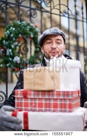 Man blowing snow away from a stack of Christmas presents