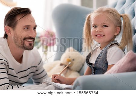 I like studying. Cheerful cute diligent girl holding a pencil and looking at you while enjoying her home lesson