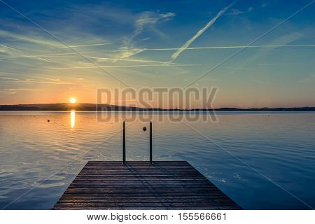 Relaxing quiet evening on the lake. Setting sun is reflected in water. Switzerland.
