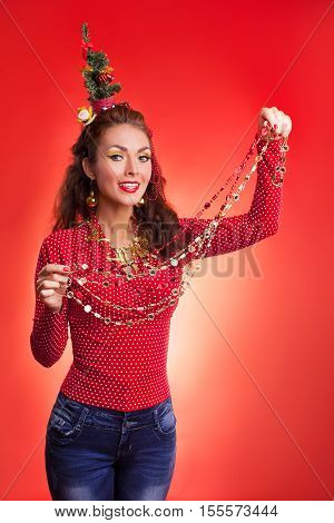 New Year's and Christmas efforts and preparations.Smiling Girl with New Year tree instead of santa hat on head thinks about winter holidays celebration and holding garland decoration in hand. Woman arranging decorations of Xmas tree. Creative fun studio p