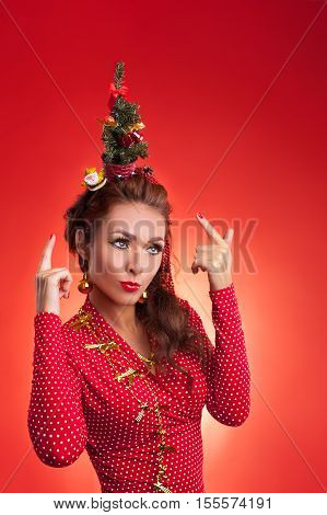 New Year's and Christmas efforts and preparations. Girl with New Year tree instead of santa hat on head thinks about winter holidays celebration. Woman arranging pointing to Xmas tree. Creative fun studio photo.