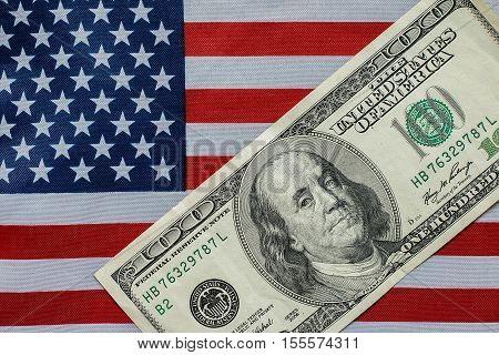 A hundred dollar bill in front of the American flag