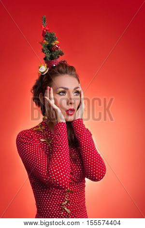 New Year's and Christmas efforts and preparations. Surprised Girl with New Year tree instead of santa hat on head remembered about winter holidays celebration. Woman arranging decorations of Xmas tree. Creative fun studio photo.