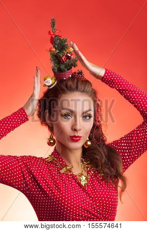 New Year's and Christmas efforts and preparations. Girl with New Year tree instead of santa hat on head thinks about winter holidays celebration. Woman arranging decorations of Xmas tree. Creative fun studio photo.