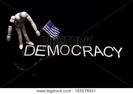 Grieving Democracy. The model of a man or woman holding a USA flag stands over the word democracy. Its head is bowed and it is wearing a black armband.