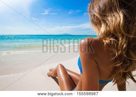Woman in bikini sitting on the beach at sunny day