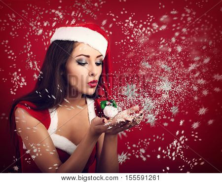 Beautiful Makeup Happy Woman In Santa Claus Costume Blowing On Snowflake In Her Hands On Bright Red