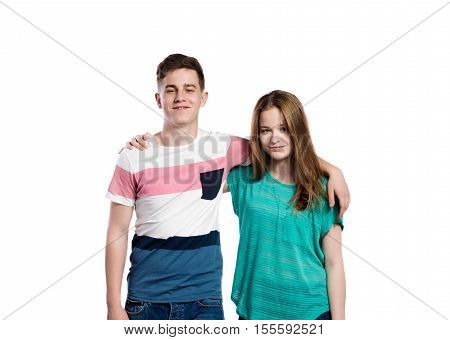 Teenage boy and girl with arms around each other, smiling. Young woman in green t-shirt holdidng man in striped t-shirt. Studio shot on white background, isolated.
