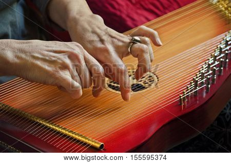Playing music on lap harp in closeup view