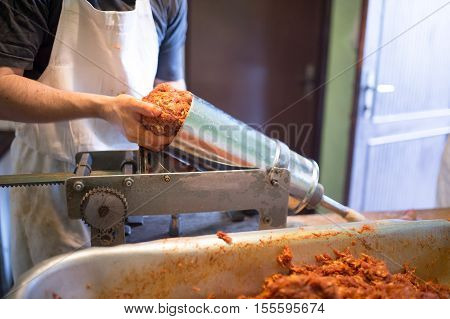 Unrecognizable man making sausages the traditional way at home. Putting meat ball into sausage filler. Close up.