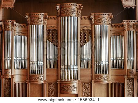 Beautiful wooden facade of a large modern organ with oak carving in the concert hall