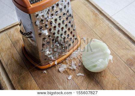 Half grated onion near metal standing grater on wooden cutting board
