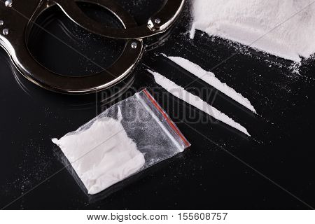 Handcuffs And Cocaine On Black Background