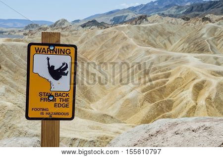 Warning sign at Zabriskie Point furnace creek formations in Death Valley National Park, California, USA