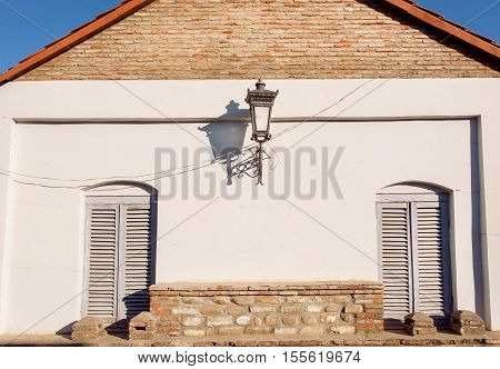 Antique lamp post on brick wall with two closed windows. Old house background
