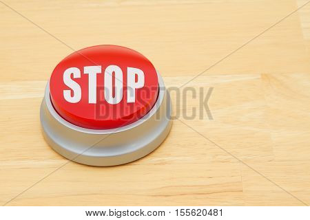 A Stop red push button A red and silver push button on a wooden desk with text Stop
