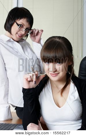 The charming business woman with colleagues at office