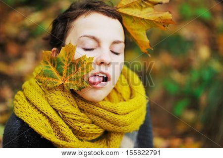 Young teen girl in a knitted scarf with maple leaves in her hair grimaces showing language.